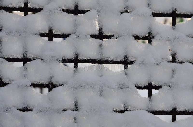 Die grafische Ressource besteht aus einem Metallgitter, das mit Schnee umfasst wird lizenzfreie stockbilder