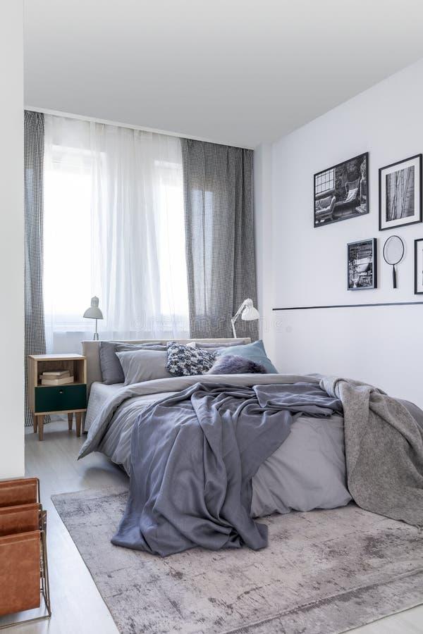 Die grauen Blätter auf Bett und kopiert drapiert am Fenster im Schlafzimmerinnenraum mit Plakaten Reales Foto stockfotos