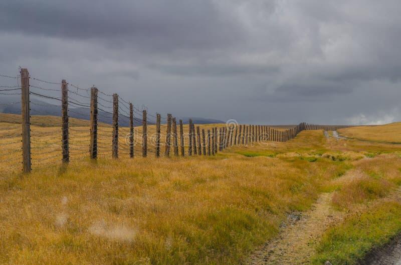 Die Grenze Eines Bretterzauns Mit Stacheldraht Und Wolken Stockbild ...