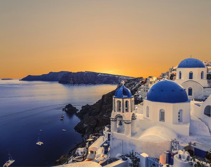 Die griechisch-orthodoxe Kirche auf dem Hintergrundwasser des Ägäischen Meers in Oia bei Sonnenuntergang Die Insel von Santorin stockfotografie