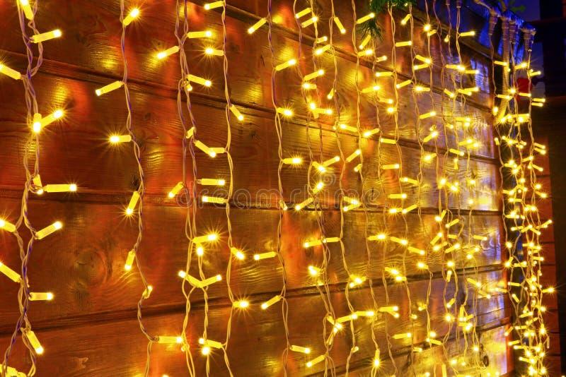 Die große lange Girlande der gelben Farbe schön und belichtet hell hölzerne Bretter Wand, Zaun auf fröhlichem und romantischem ho lizenzfreie stockbilder