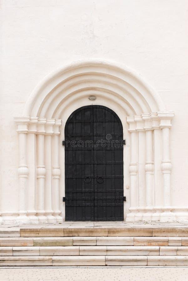Die große schwarze Tür ist das Tor zum weißen Gebäude Träger werden im Glas des Einkaufszentrums reflektiert stockbild