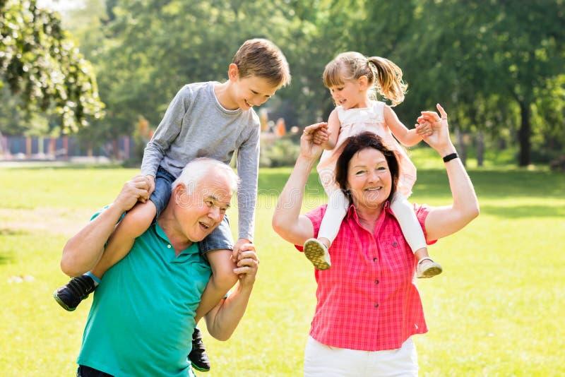 Die Großeltern, die Enkelkinder geben, tragen Fahrt huckepack lizenzfreies stockfoto