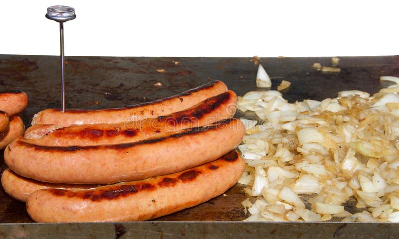Die großen Hotdogwürste, die nahe bei gehackten Zwiebeln auf einem bbq im Freien grillen, grillen lizenzfreie stockfotografie