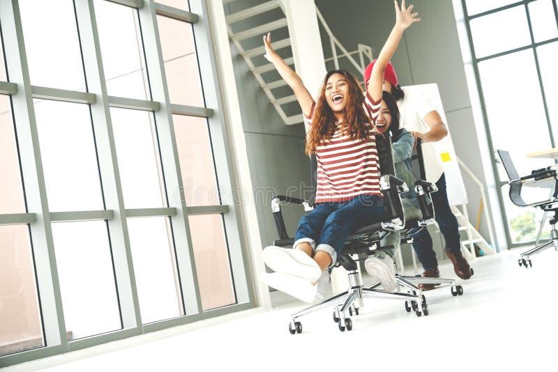 Die Gruppe multiethnische junge kreative Teamwork, die Spaß lachend und lächelnd im Büro hat, sitzt dem Druck vor Mitarbeiter, de lizenzfreies stockfoto