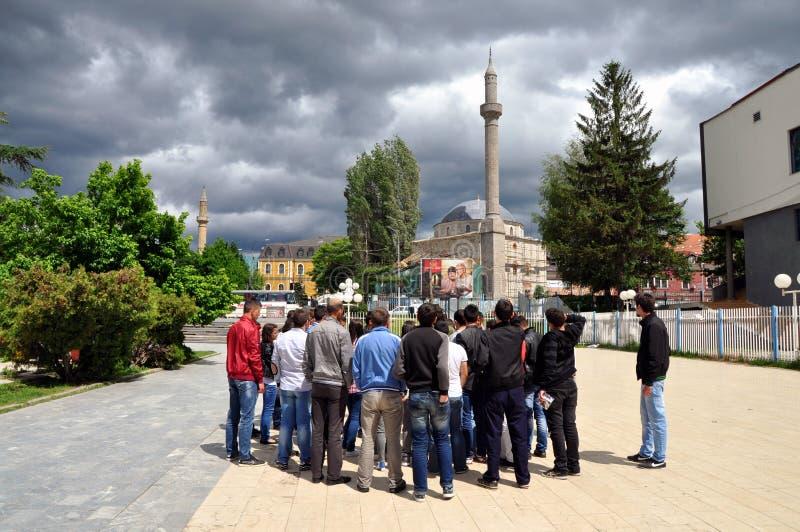 Die Gruppe von den ausländischen Touristen, die das alte Teil von Prishtina besuchen stockfotografie