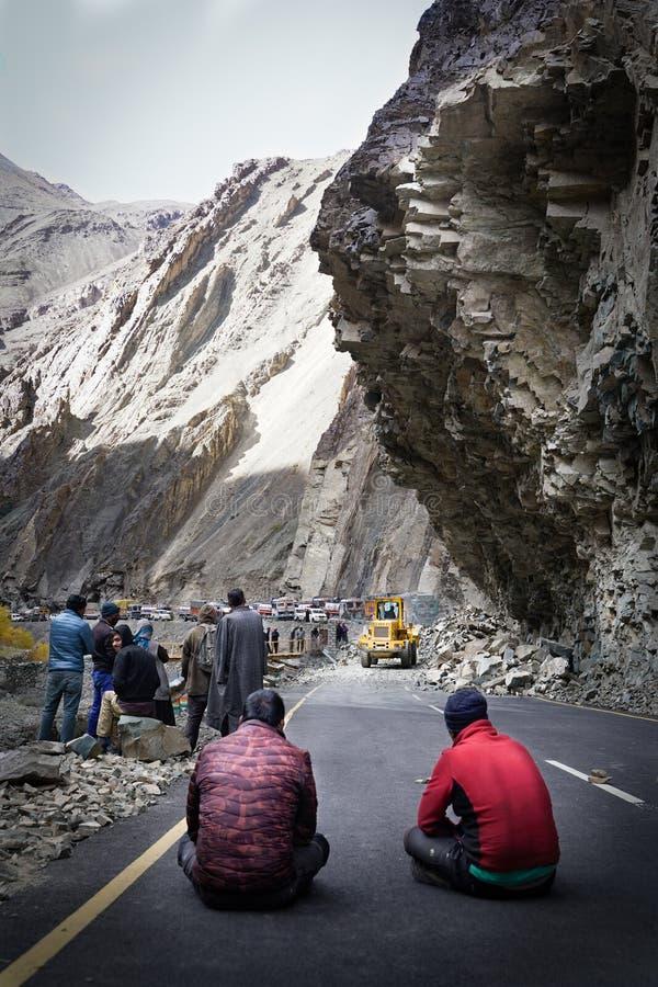 Die Gruppe von den LKW-Fahrern, die warten, wenn die Straße wegen des Erdrutschs klar ist lizenzfreies stockfoto