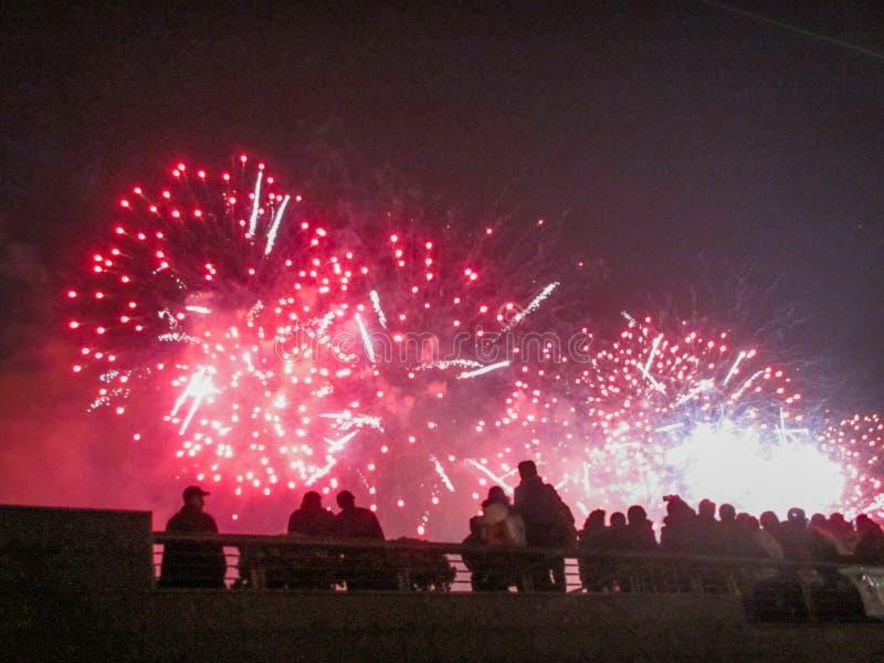 Die Gruppe von Personen, die großartige rote Feuerwerke genießt, zeigen in einem Karneval oder in einem Feiertag stockbilder