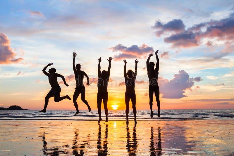 Die Gruppe von Personen springend auf den Strand bei Sonnenuntergang, Schattenbilder von glücklichen Freunden stockfotografie