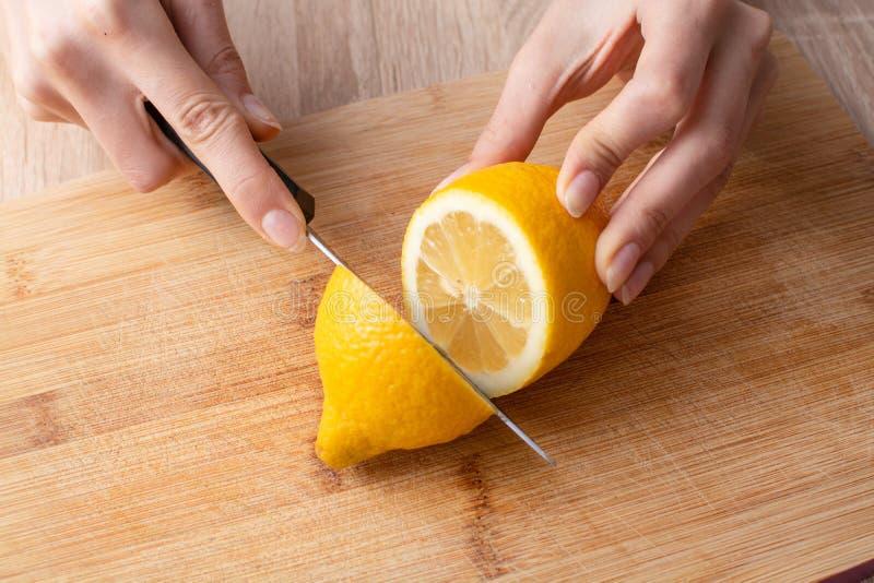 Die Hände der Frauen, die eine Zitrone zur Hälfte auf dem hölzernen Schneidebrett cuting sind lizenzfreies stockbild