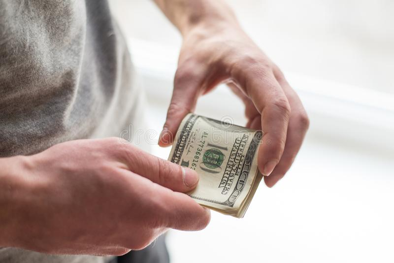 Die Hände des Mannes mit Dollar auf weißem Hintergrund Taschenrechner- und Goldmünzen stockfotografie