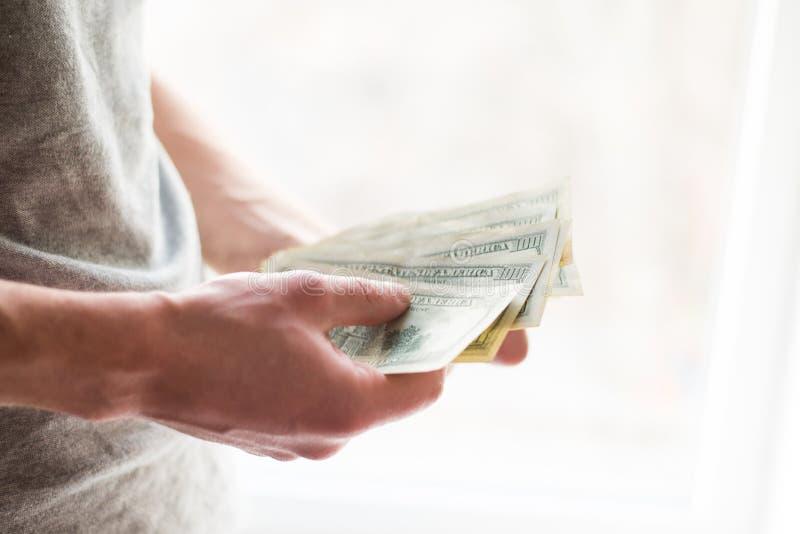 Die Hände des Mannes mit Dollar auf weißem Hintergrund Taschenrechner- und Goldmünzen giva ein Bestechungsgeld stockfoto