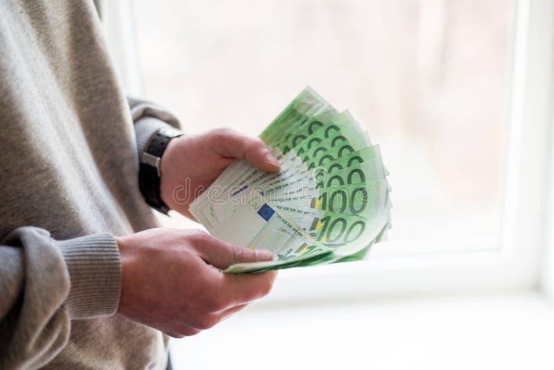 Die Hände des Mannes mit Euro auf weißem Hintergrund Taschenrechner- und Goldmünzen stockbild