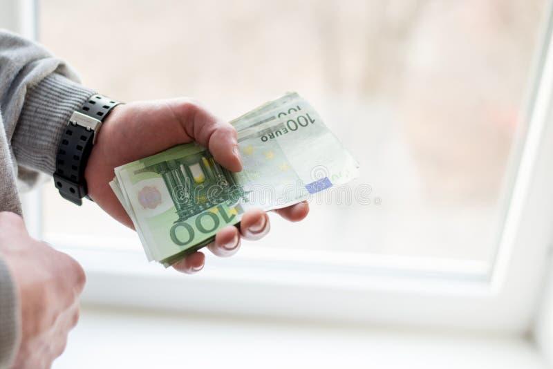 Die Hände des Mannes mit Euro auf weißem Hintergrund Taschenrechner- und Goldmünzen stockfoto