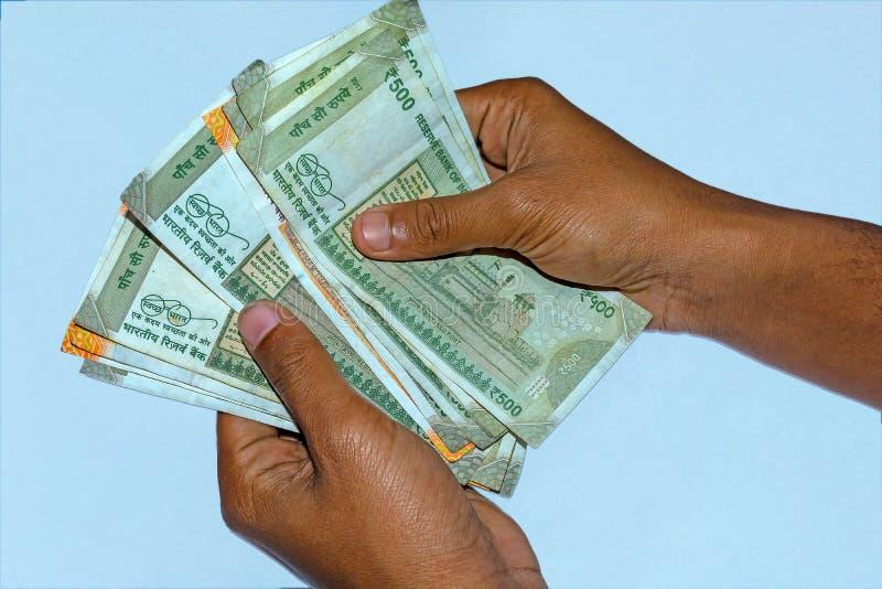 Die Hände des Mannes, die neue 500 und 200 Rupien indische Währung halten und zählen stockbilder