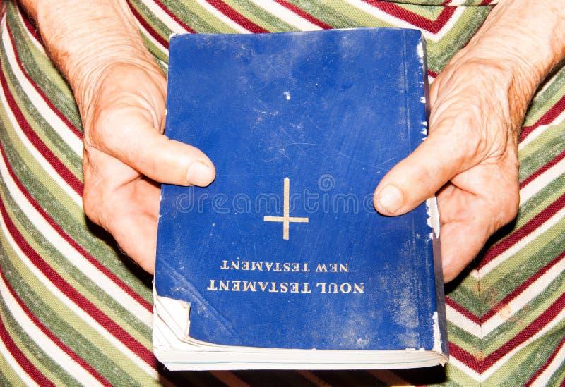 Die Hände der älteren Frau, die eine alte Bibel halten stockfoto