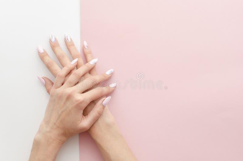 Die Hände der Draufsichtfrau maniküren mit malender Arbeit des Nagels Zeichnung auf Nagelfahnenkonzept für einen Schönheitssalon  stockfoto