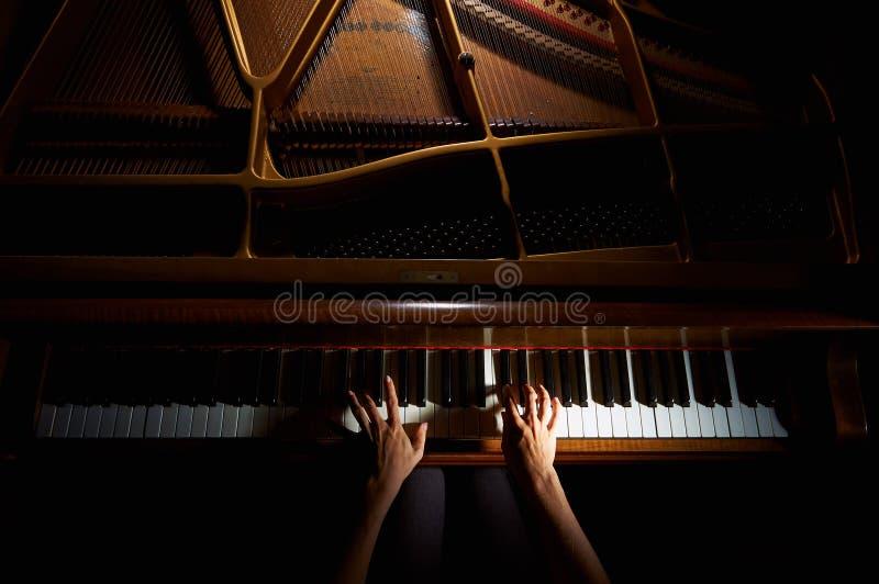 Die Hände der Frau auf der Tastatur des Klaviers in der Nachtnahaufnahme stockfotografie