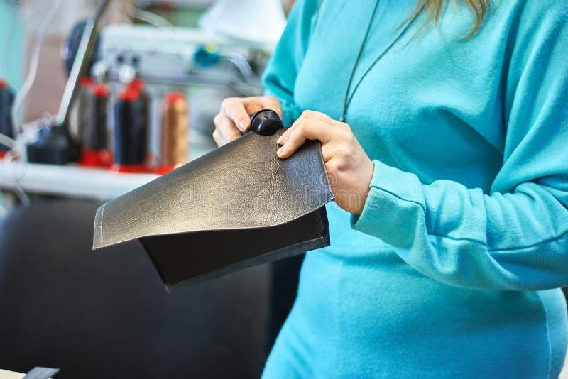 Die Hände der Frau, die ein Stück Leder halten Fertigung von handgemachten Taschen lizenzfreies stockfoto