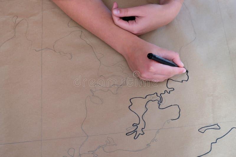 Die Hände der Frau, die eine Karte der Welt auf Brauenpapier zeichnen stockfoto