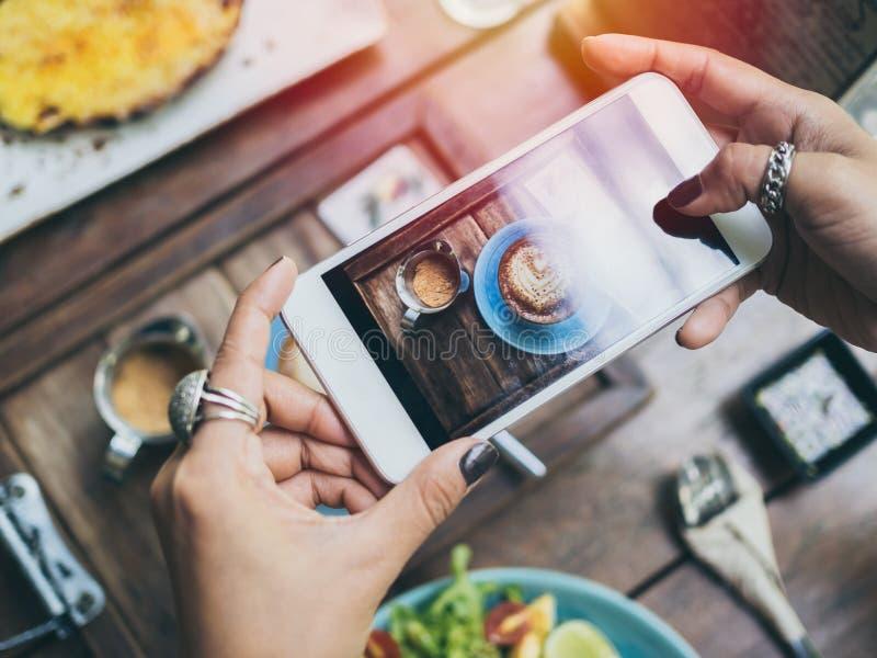 Die Hände der Frau, die Foto der Kaffeetasse auf Holztisch durch Smartphone machen stockbilder