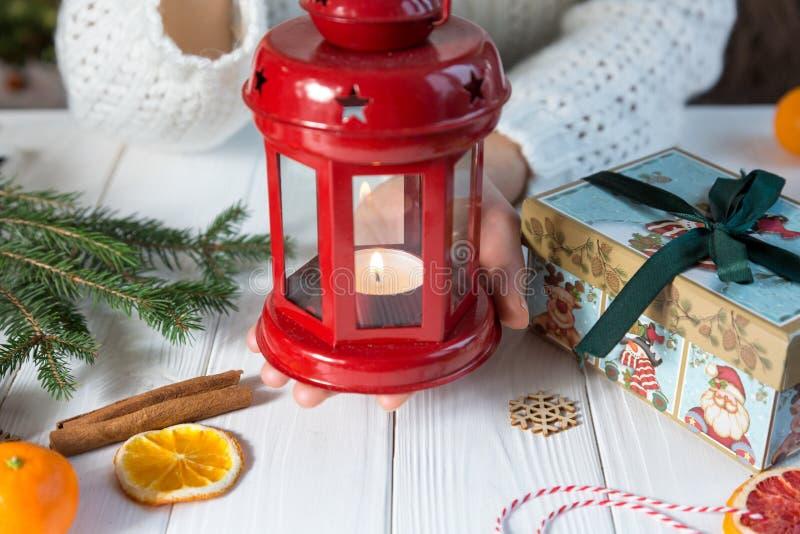 Die Hände der Frau halten rote Laterne auf weißem woode Hintergrund Wintervorbereitung, neues Jahr und Weihnachtsfeier lizenzfreies stockfoto