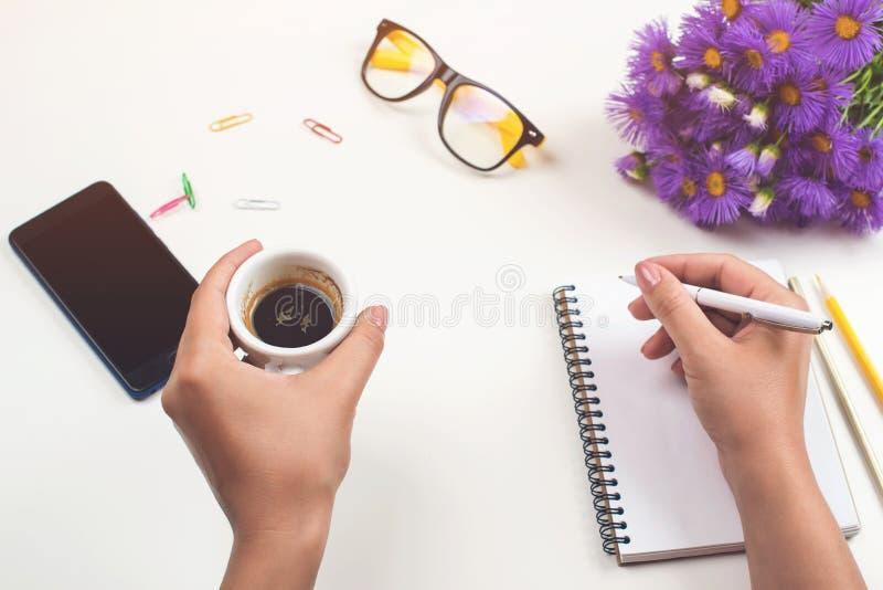 Die Hände der Frau mit Kaffee auf Schreibtisch Arbeitsplatz mit Notizbuch, Telefon, Gläser, Stift, lila Blumen, Tasse Kaffee Flac stockfoto