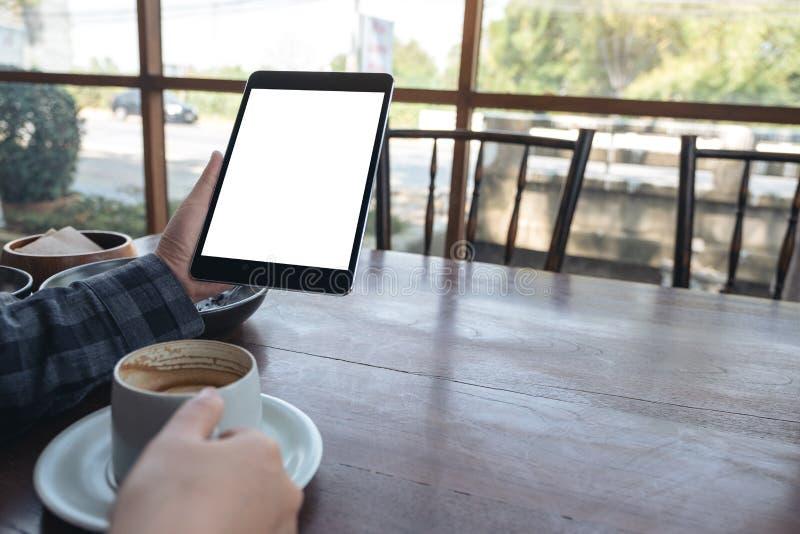 Die Hände der Frau, die schwarzen Tabletten-PC mit leerem Bildschirm beim Trinken des Kaffees auf Holztisch im Café halten stockfoto