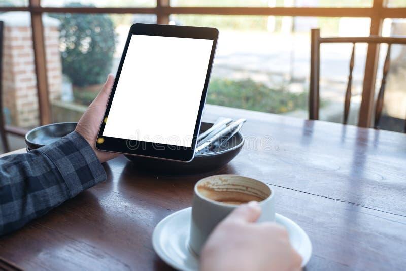 Die Hände der Frau, die schwarzen Tabletten-PC mit leerem Bildschirm beim Trinken des Kaffees auf Holztisch im Café halten lizenzfreie stockfotografie