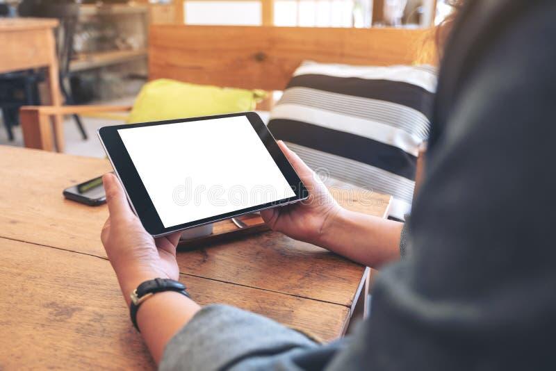 Die Hände der Frau, die schwarzen Tabletten-PC mit leerem Bildschirm horizontal auf Holztisch im Café halten lizenzfreies stockbild