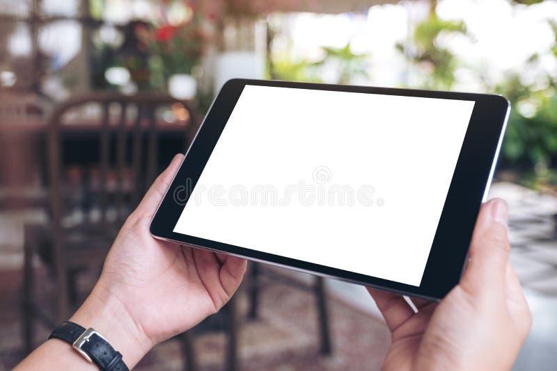 Die Hände der Frau, die schwarzen Tabletten-PC mit leerem Bildschirm horizontal im Café halten lizenzfreie stockfotos