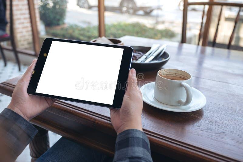 Die Hände der Frau, die schwarzen Tabletten-PC mit leerem Bildschirm horizontal mit Kaffeetasse auf Holztisch im Café halten stockfotos