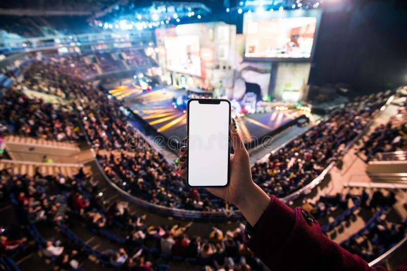 Die Hände der Frau unter Verwendung der digitalen Anwendung am intelligenten Mobiltelefon an esport Ereignis an der großen Arena  lizenzfreie stockfotografie