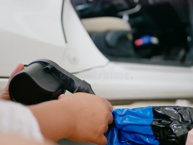Die Hände der Frau, welche die Miniluftpumpe, angeschlossen an den Autostecker, um eine Schwingpuppe aufzublasen halten und verwe lizenzfreies stockfoto