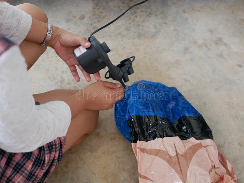 Die Hände der Frau, welche die Miniluftpumpe, angeschlossen an den Autostecker, um eine Schwingpuppe aufzublasen halten und verwe lizenzfreie stockfotografie