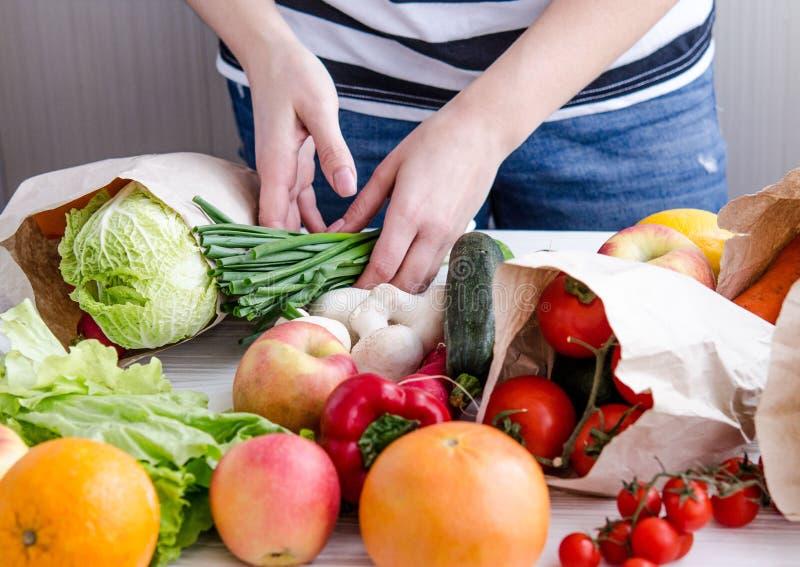Die Hände der Frauen breiten Produkte eco strengen Vegetariers aus stockbild
