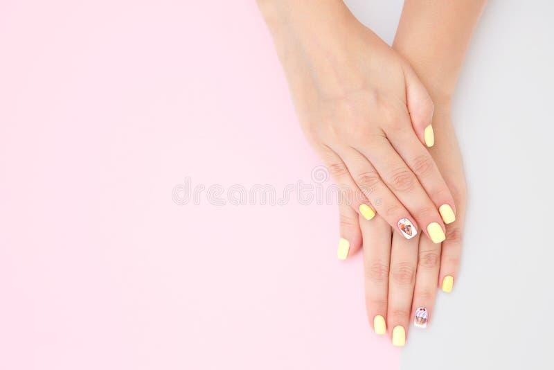 Die Hände der Frauen mit einer schönen Maniküre mit Zeichnungen von Kuchen und von Kirschen auf einem rosa-grauen Hintergrund stockfotos