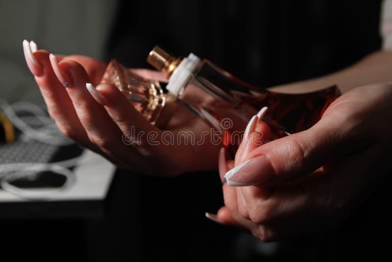 Die Hände der Frauen mit Nagelkünsten auf den Nägeln, die Flasche Parfüm halten stockfoto