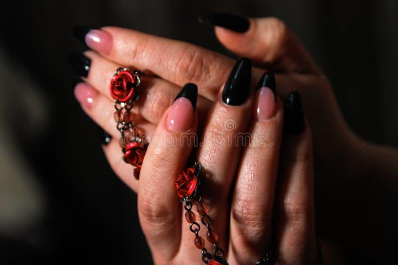 Die Hände der Frauen mit Nagelkünsten auf den Nägeln, die Modeschmuck halten lizenzfreie stockbilder