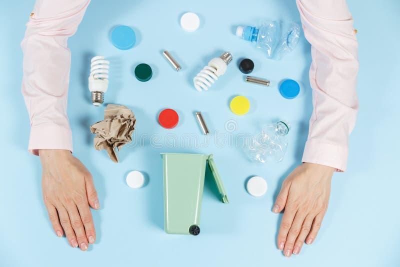 Die Hände der Frauen sortieren den Abfall Ökologiekonzept, viele recyclebaren Gegenstände in den Behältern auf dem Farbhintergrun stockfoto