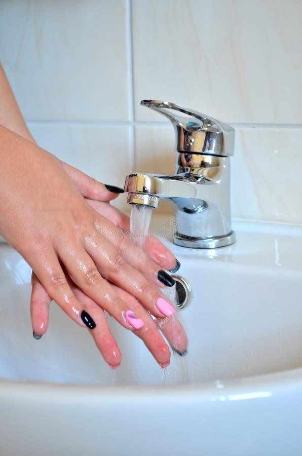 Die Hände der Frauen, die unter Wasser mit einem Hahn gewaschen werden, vertikale Orientierung stockbild