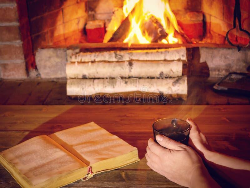 Die Hände der Frauen wärmen auf einer heißen Tasse Tee nahe einem brennenden Kamin, ein offenes Buch ist auf dem Tisch auf stockfoto