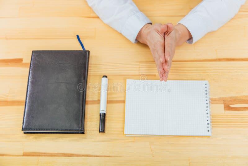 Die Hände der Jungefrauen im Büro auf dem Tisch , das Boot zum Boot auf dem Hintergrund der Tabelle faltend stockbild