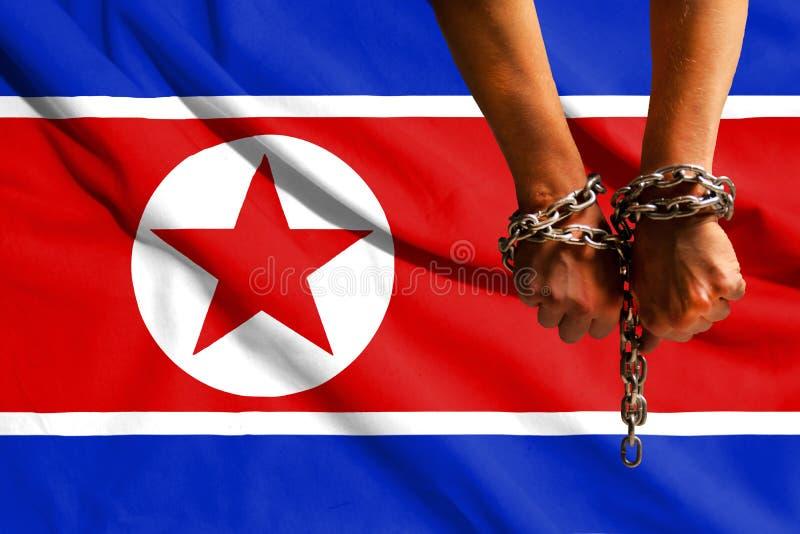 Die Hände der Ketten vor dem hintergrund der Flagge von Nordkorea, DPRK lizenzfreies stockbild