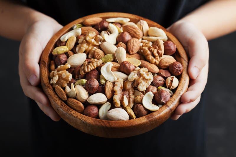 Die Hände der Kinder, die eine hölzerne Schüssel mit Mischnüssen halten Gesundes Lebensmittel und Snack Walnuss, Pistazien, Mande stockfotos