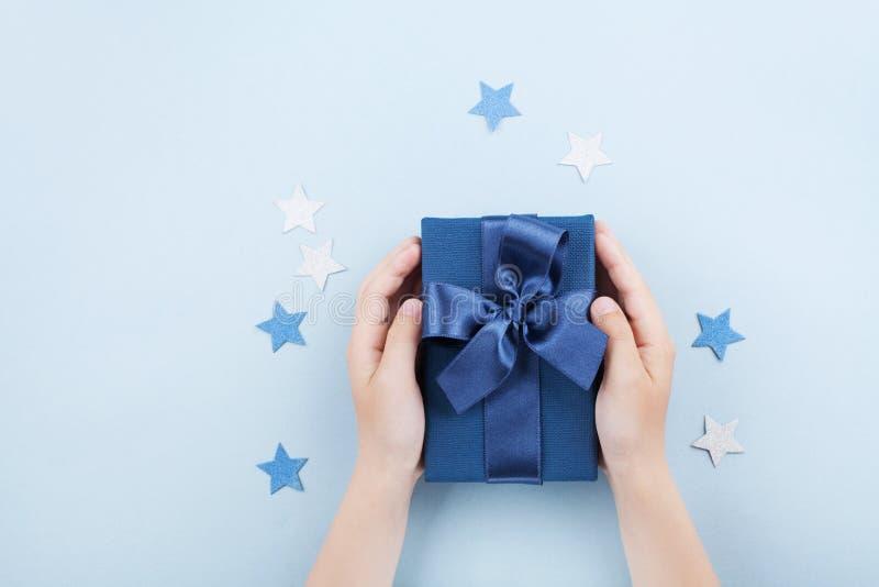 Die Hände der Kinder, die ein Geschenk oder einen Präsentkarton halten, verzierten Konfettisterne auf blauer Tischplatteansicht stockbilder