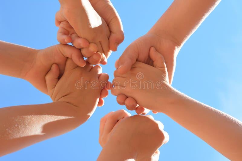 Die Hände der Kinder halten sich herum auf einem Hintergrund des blauen Himmels lizenzfreie stockbilder