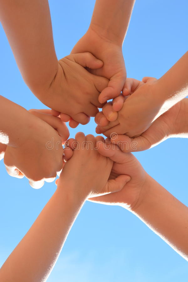 Die Hände der Kinder halten sich herum auf einem Hintergrund des blauen Himmels lizenzfreies stockbild