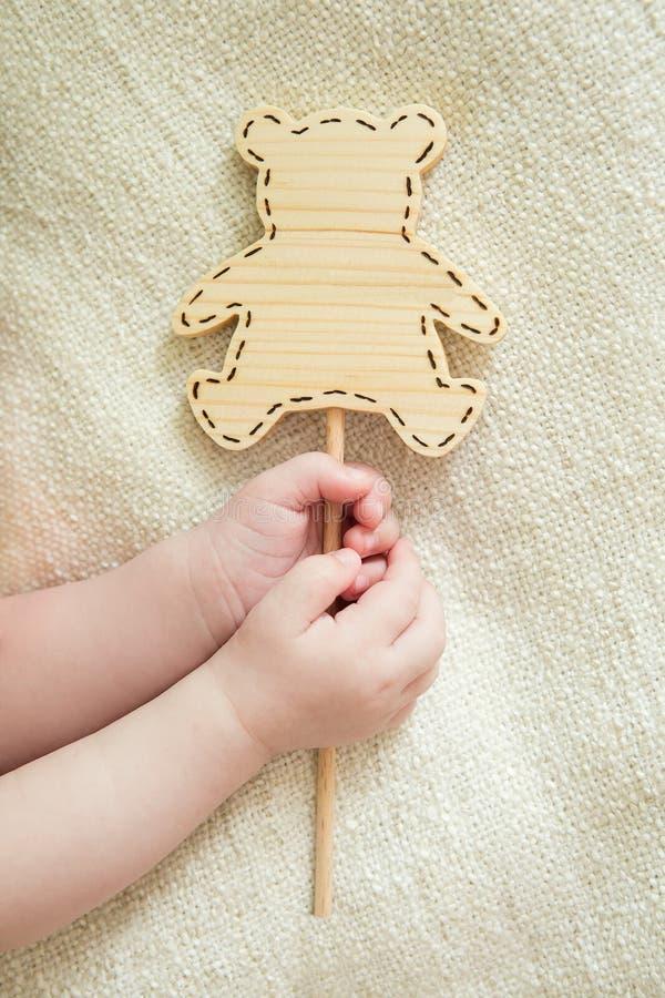 Die Hände der kleine Kinder halten die hölzerne Tablette stockbild