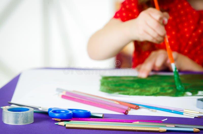 Die Hände der Mädchen, die Pinselmalerei halten stockbilder